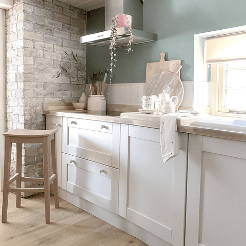 the kitchen features a gorgeous muted green feature wall