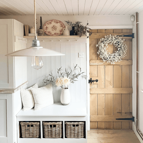 A bench seat with storage baskets and peg shelving make clever use of the limited space in this little room, proving that small is almost always beautiful.