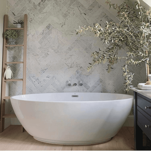 The herringbone Italian Carrara marble tiles in the bathroom are just stunning and perfectly complement the modern, free-standing tub