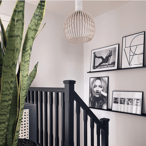 Black and white prints line the stairway, along with stylish black banister railings, which Holly painted herself.