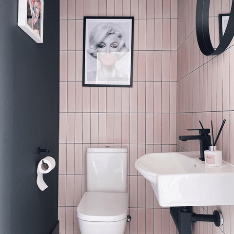 This bathroom is our favourite spot in the house, with its geometric pink tiling, bold black feature wall and matching sink fittings