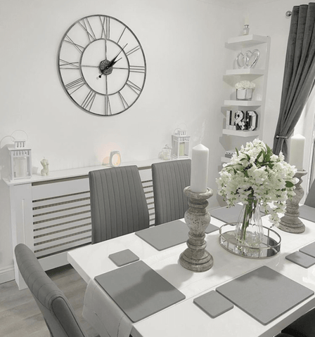 In the dining room, stone candlesticks and place settings create a cool, modern vibe, while a supersized metal wall clock dominates the view