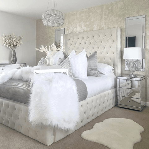 The ultra glamourous bedroom has a stunning central chandelier over a bed that's made up with a set of Hampton and Astley Egyptian cotton sateen bedding.
