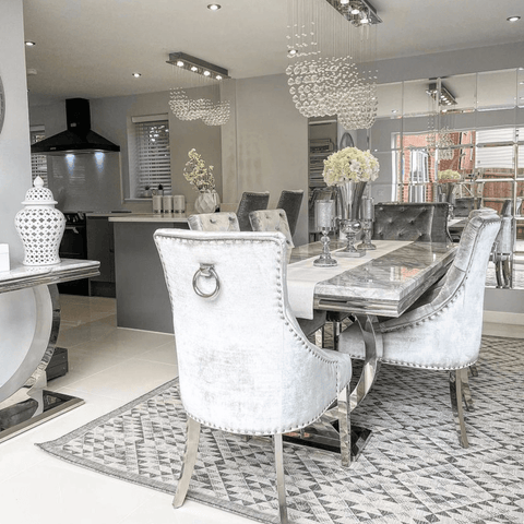 More eye-catching chandeliers light up the open plan kitchen diner, which features a table that looks fit for a king