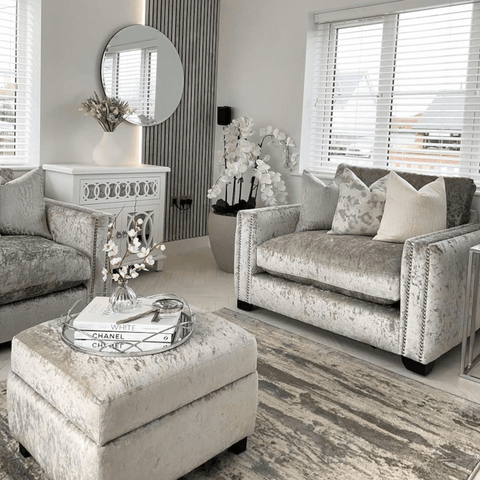 Soft silver sofas and white flower arrangements add an elegant touch to the living area