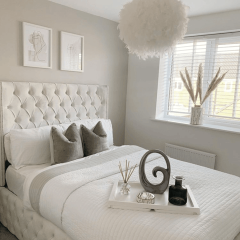 We just love the way this feathered light shade adds a fun touch of glamour to this beautifully serene bedroom