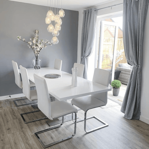 A 12-bulb statement light makes a stunning centerpiece to the dining room, complemented by modern gloss white furniture and soft grey décor