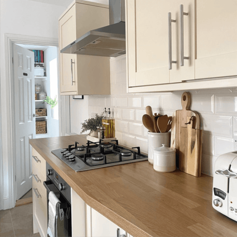 Oak worktops and shaker style cabinets create a modern country vibe in the kitchen.