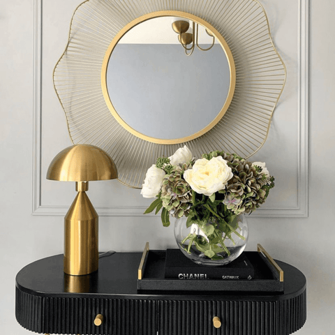 We love this stylish black console table with its eye-catching brass lamp and gorgeous brass-rimmed wall mirror.