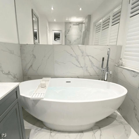 The stunning marble walled bathroom features an envy-inducing freestanding tub and is lit up by a Hampton and Astley Bergamot, Rose and Lavender candle