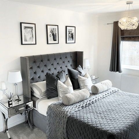 In the monochrome master bedroom, the beautiful grey bed is layered with cosy and inviting bed linens