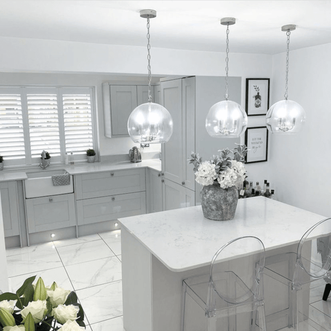 Vases of white flowers add life to the newly extended kitchen, along with three gorgeous glass orb pendant lights