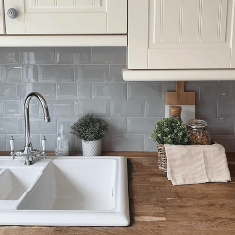 A white sink set against real natural worktops and pale grey metro tiles create a relaxed vibe in the country style kitchen