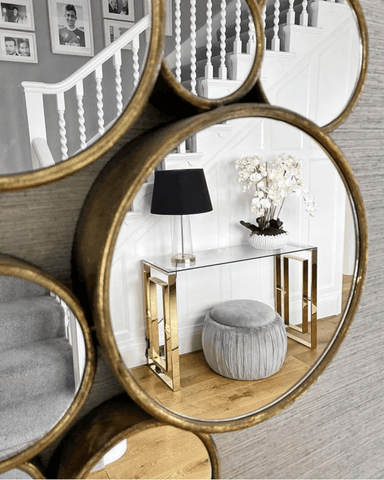 A stunning gold-effect multi circle wall mirror and console table bring character to the hallway