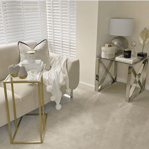 Brass occasional tables and touches of gold décor add glamour to the living room, creating the perfect spot to catch up with friends