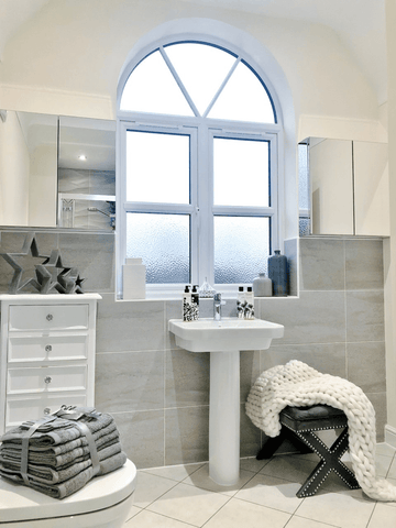 A stunning arched window flanked by mirrored cabinets form the centrepiece of the bathroom