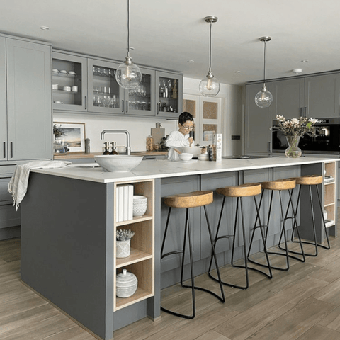 The extended kitchen is a beautifully modern mix of white and soft greys, with an extra long central island that will be envy of chefs everywhere