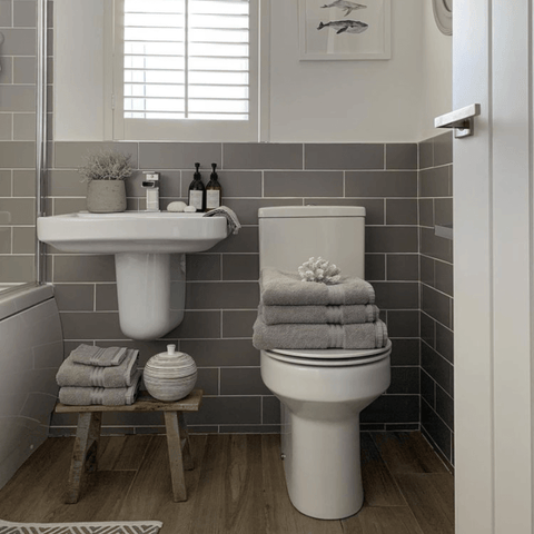 White furniture, chrome fittings and mid-grey metro tiles make a smart combination in this bathroom, which features a stack of Hampton and Astley Egyptian cotton towels in subtle grey