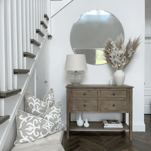 In the hallway, a rustic wood console table is complemented by simple white accessories and a pampas grass filled vase.