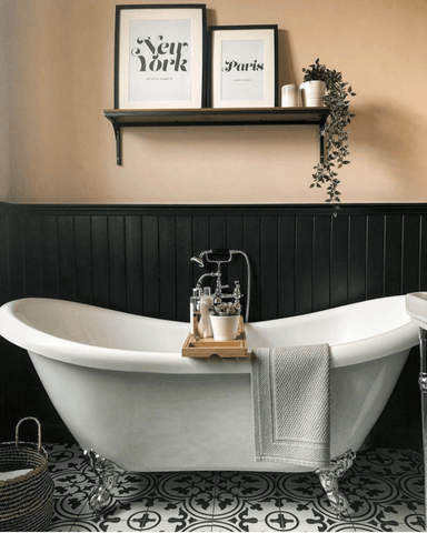 This theme continues in the bathroom, where black paneling and patterned floor tiles make the perfect backdrop for the elegant Victorian slipper bath