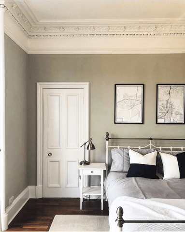 The master bedroom is painted a gorgeous muted green that looks effortlessly classy behind the iron bed frame, which features Hampton and Astley long-staple cotton sateen bedding in subtle grey