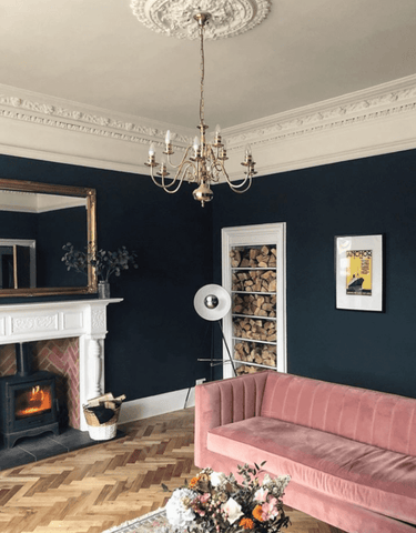 n the living room, inky blue walls and a herringbone wood floor complement the Victorian style fireplace