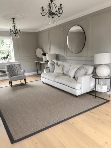 More chandeliers and paneling await in the elegantly decorated sitting room, which has soft grey walls, a classic white sofa and circular glass side tables