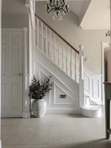 A traditional style staircase with paneled walls and an eye-catching chandelier create a fabulous first impression in the entrance hallway