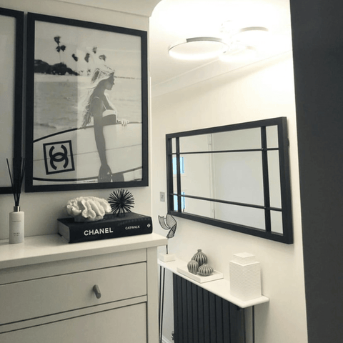 This monochrome theme extends throughout the rest of the home, with a black radiator, picture frames and mirror striking a contrast in the hallway.