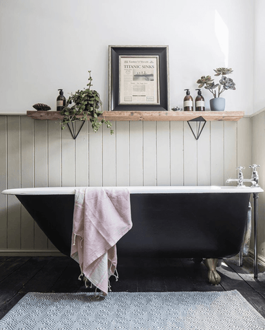 Upstairs the bathroom features a striking standalone Victorian style bathtub, panelled walling and a rustic wood shelf.