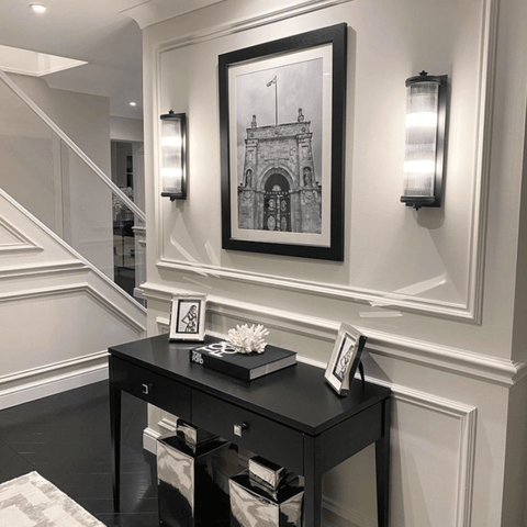 Black chevron wood flooring and a framed print of Blenheim Palace look super stylish in the black and white themed hallway