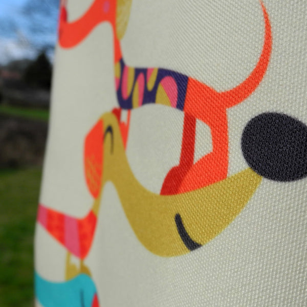 Close up of Dashing Dachshunds apron in cream by Rollerdog