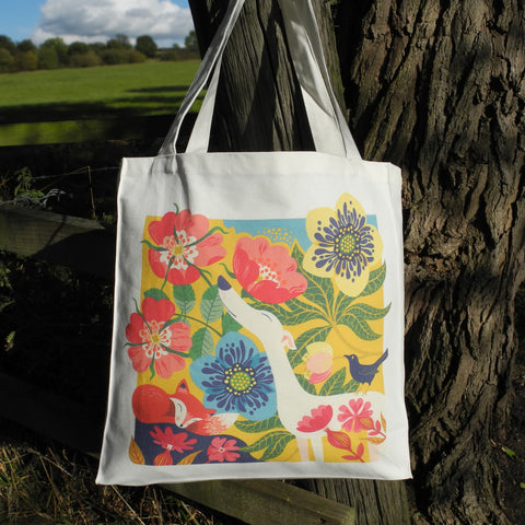 A tote bag with Rollerdog's Dog Rose design, hanging from a fence post in the countryside