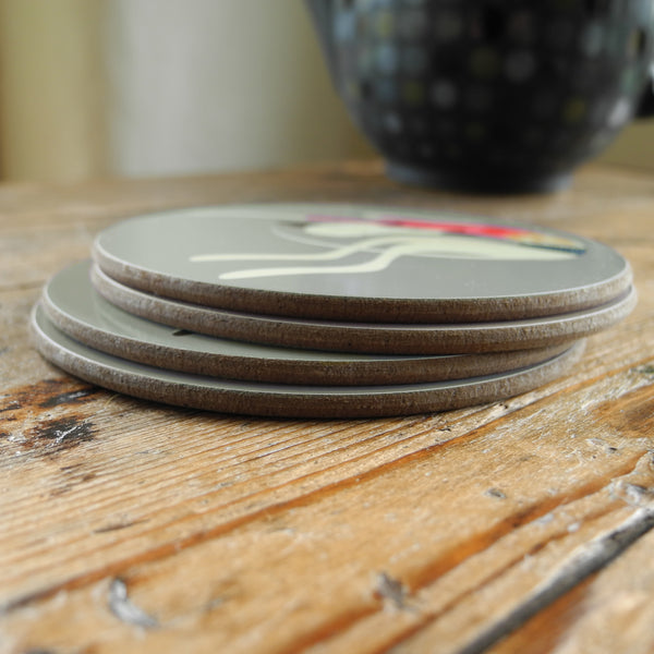 A stack of 4 Rollerdog Greyhound & Whippet coasters on a wooden surface