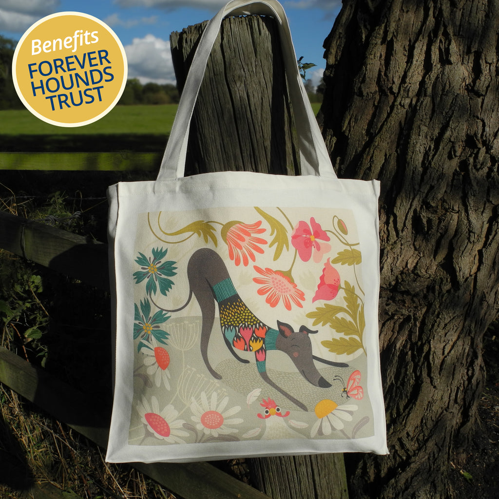 a Rollerdog tote bag printed with the Greta design, shown hooked on a fence in the countryside