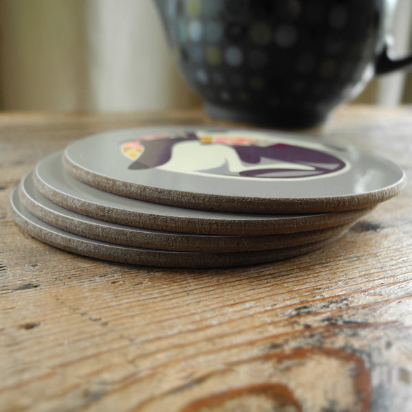 A stack of 4 Rollerdog coasters on a wooden surface