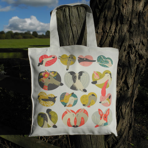 A Noses and Poses tote bag by Rollerdog, hanging on a  fence post in the countryside