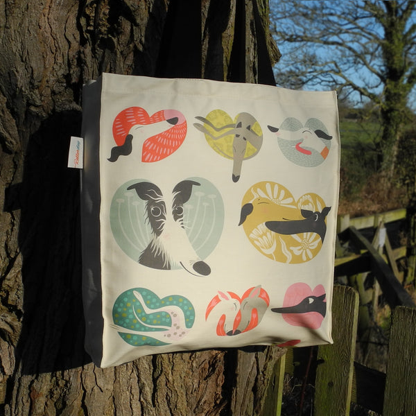 The back view of a Noses & Poses tote bag by Rollerdog, next to a tree in the countryside