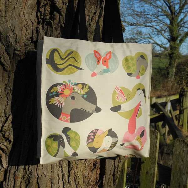 A Noses & Poses tote bag by Rollerdog, next to a tree in the countryside