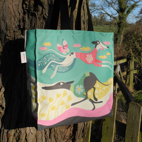 A Zoomies tote bag by Rollerdog, shown outside next to a tree