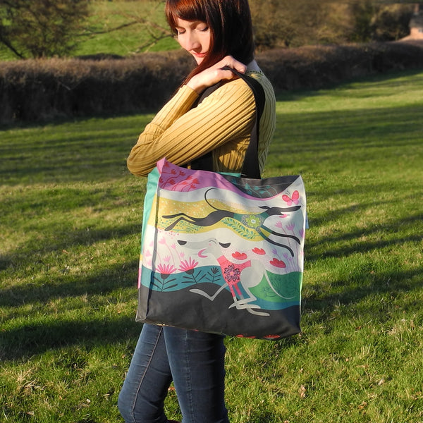 A Zoomies tote bag shown in use as a shoulder bag