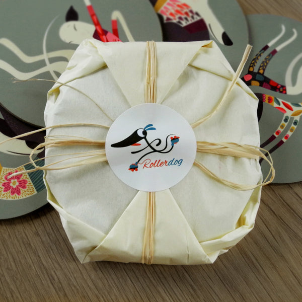 A set of Rollerdog coasters wrapped in tissue paper and raffia