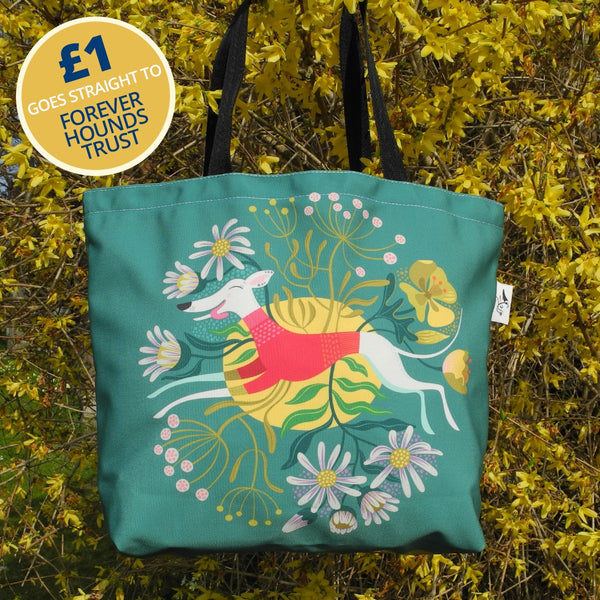 Snowy the Whippet tote bag against yellow flowers, with £1 going to Forever Hounds Trust