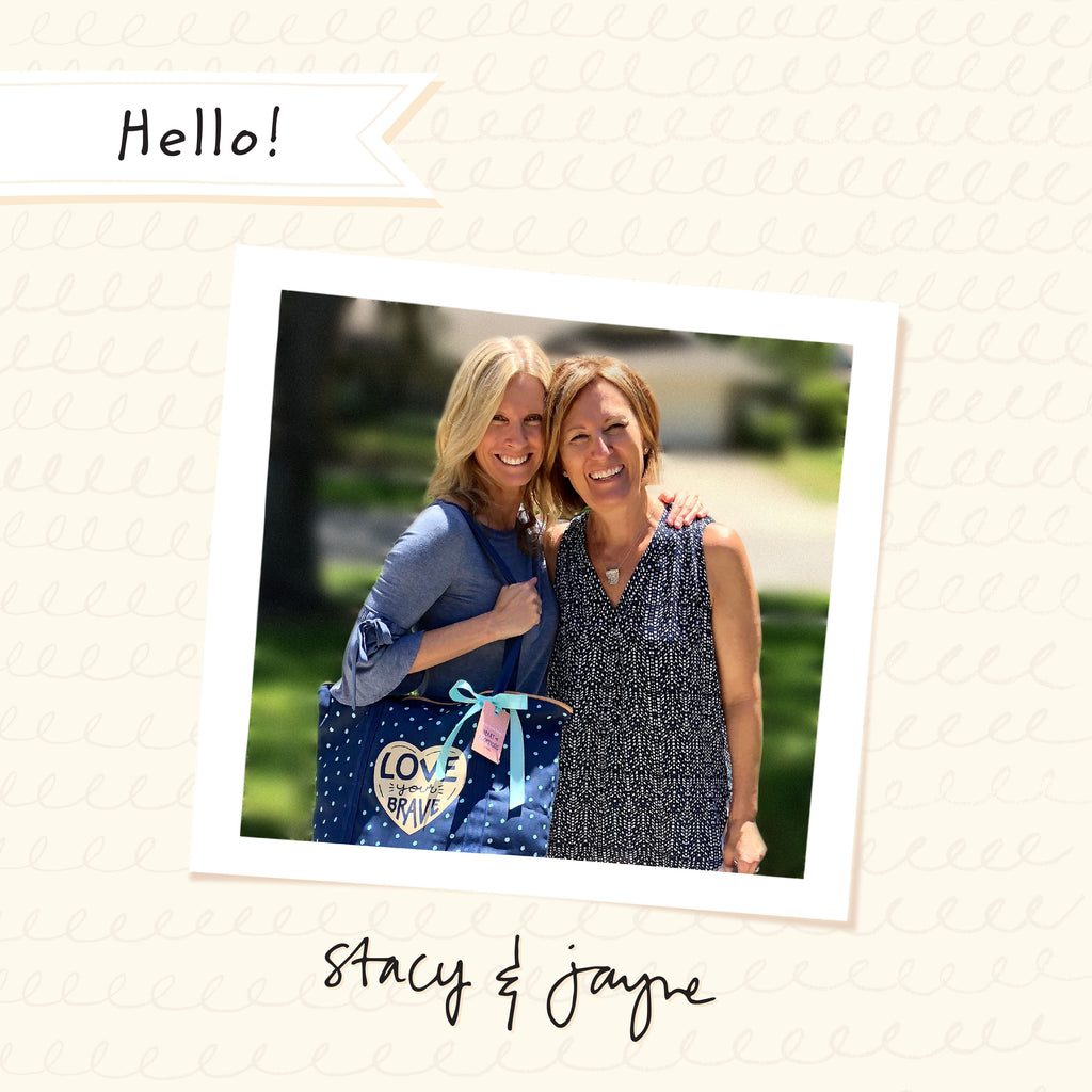 Photo of the two co-founders of Tiny Type Studios and the creators of Adoptionly Yours Cards & Gifts. Stacy on the left has her arm around Jayne on the right and Stacy is shouldering a Love Your Brave birth mother tote.