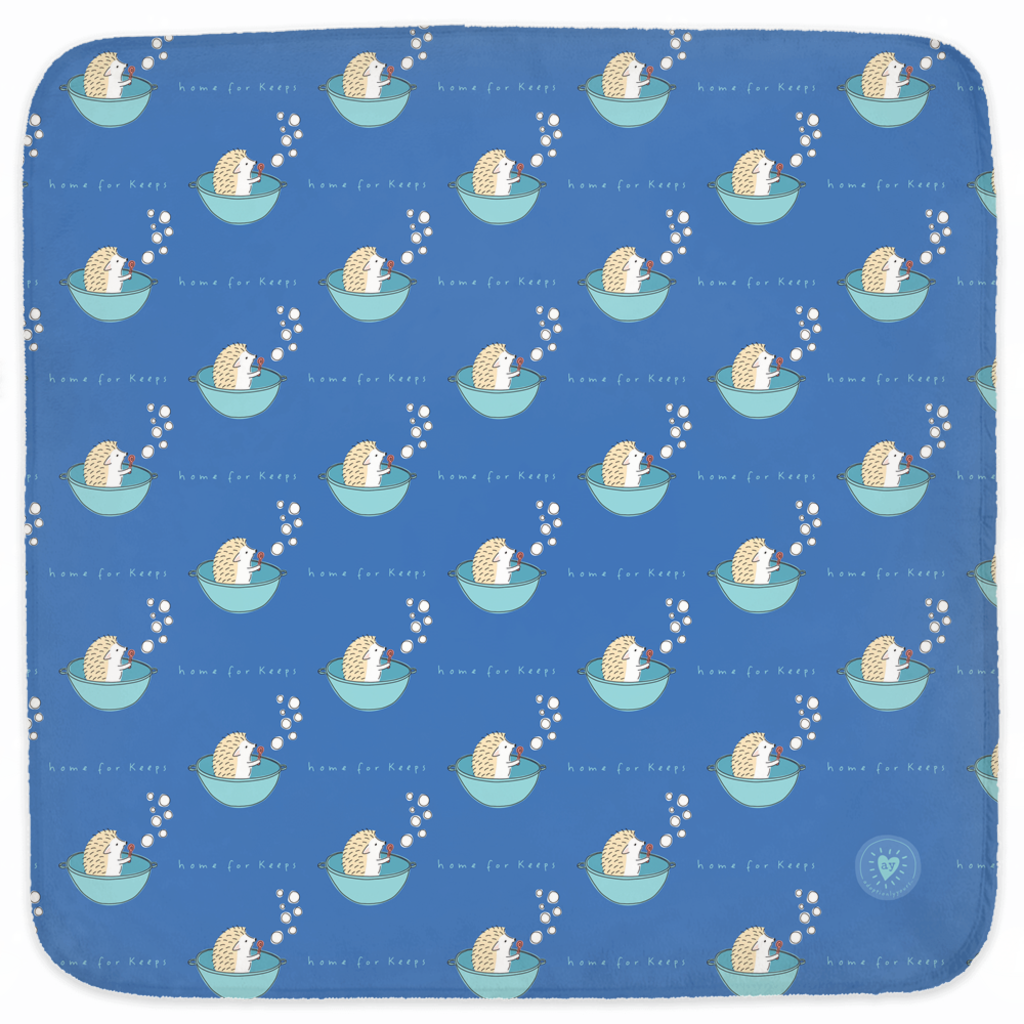 30 by 30 inch rounded corner, soft polyester fleece with white cotton loop towel on back. Royal blue background. Pattern of hand drawn hedgehog sitting in a bright teal tub and holding a red bubble wand with six bubbles floating up. About 10 rows of 4 hedgehogs in tub make up the pattern. The words home for keeps sit below each tub. A small adoptionly yours heart logo in the lower right. Backside has a rectangle hood with a drawing of the hedgehog from the nose up.