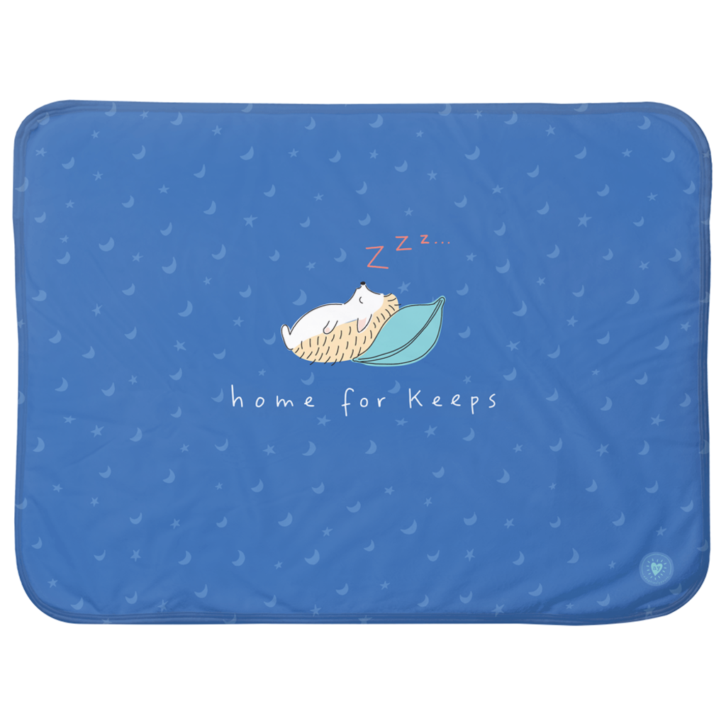 30 by 40 inch sherpa blanket with super soft 100% polyester on one side and tan fleece backing on the other side. Front of blanket has royal blue background with hand drawn light blue moon and stars pattern. Centered on front of blanket is a hand drawn hedgehog lying on his back with head resting on a teal colored pillow. Red colored Z's are rising from his nose. The words home for keeps in white hand lettering rest below hedgehog's back. A small light blue adoptionly yours logo in lower right corner.