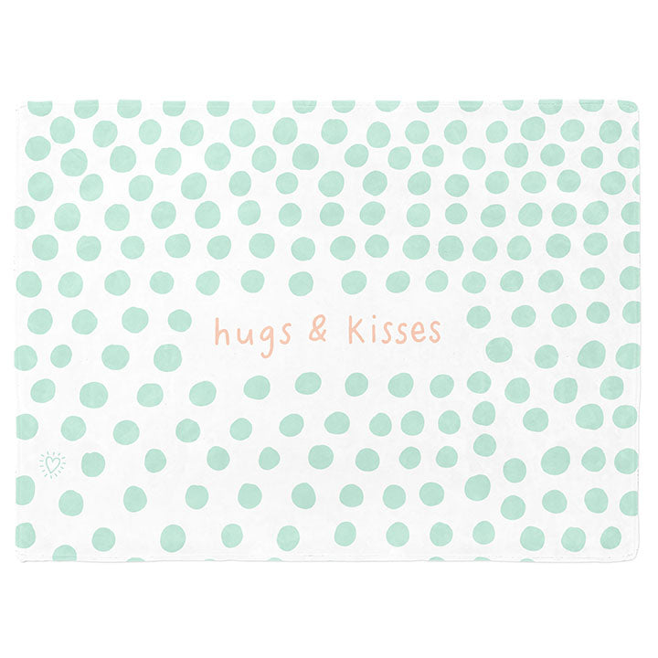 30 by 40 inch silky-soft fleece blanket that is hypoallergenic. Perfect size for a toddler or child. Bright white blanket printed on one side only. 3 inch hand drawn mint green dots scattered across blanket with the words hugs & kisses hand drawn in a peach color. A small Adoptionly Yours heart logo by itself in mint green in lower left corner of blanket on front.