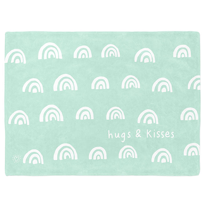30 by 40 inch silky-soft fleece blanket that is hypoallergenic. Perfect size for a toddler or child. Bright white blanket printed on one side only. 4 rows of hand drawn rainbows in white with the words hugs & kisses hand drawn in white on a mint green background color. A small Adoptionly Yours heart logo by itself in white in lower left corner of blanket on front.