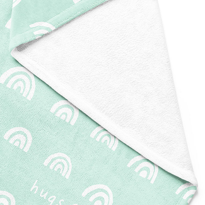 Backside of white 30 by 40 inch silky-soft fleece blanket that is hypoallergenic. Perfect size for a toddler or child. Bright white blanket printed on one side only. 4 rows of hand drawn rainbows in white with the words hugs & kisses hand drawn in white on a mint green background color. A small Adoptionly Yours heart logo by itself in white in lower left corner of blanket on front.