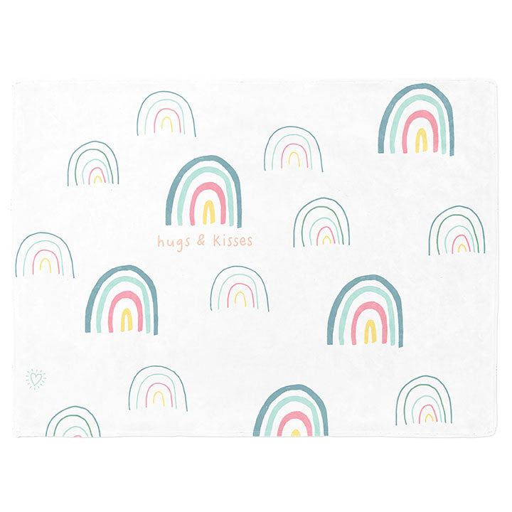 30 by 40 inch silky-soft fleece blanket that is hypoallergenic. Perfect size for a toddler or child. Bright white blanket printed on one side only. 15 large and small hand drawn rainbows scattered across blanket in magenta, light teal, bright yellow and green with the words hugs & kisses hand drawn in peach color. Adoptionly Yours heart logo by itself in light teal in lower left corner of blanket on front.